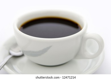 White cup of coffee with white saucer and tea spoon