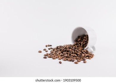 a white cup of coffee with sprinkled coffee beans