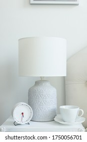 a white cup of coffee is standing on the bedside table, next to the lamp on which is a white lampshade