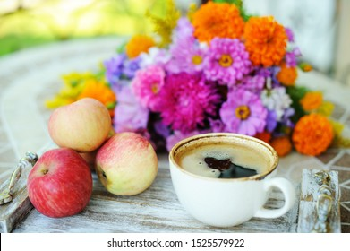 A white cup of coffee in a sunny garden on a wooden table with august flowers and apples