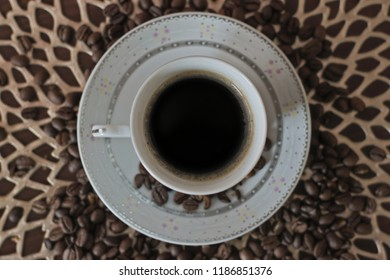 A white cup of coffee surrounded by coffie beans.