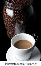 White Cup of Coffee and Toasted coffee beans in the glass pot