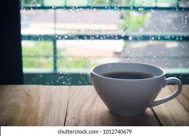 White cup of coffee,White cup of caffe on wooden table near windows in rainy day.