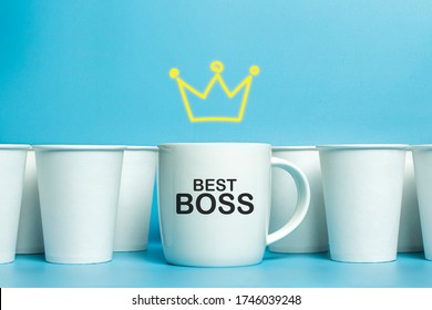 White cup with a crown drawn above it surrounded by white paper cups on a blue background. Concept boss, unique, friendly team. Copy space. Added text Best Boss