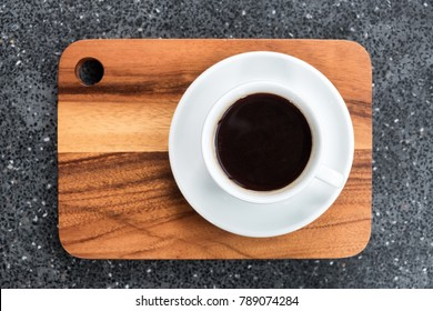 white cup of dark coffee on wooden plate on grey table, beverage