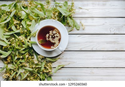 White cup and dish of linden tea on linden blossom background. Herbal medicine concept. Top view. Rustic style. Treatment of cold and flu.