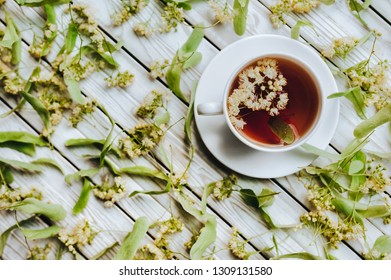 White cup and dish of linden tea on linden blossom background. Herbal medicine concept. Rustic. Top view.