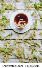 White cup and dish of linden tea on linden blossom background. Herbal medicine concept. Top view. Rustic style.