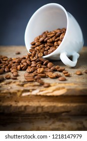 White cup with fair-trade coffee beans on wooden desk