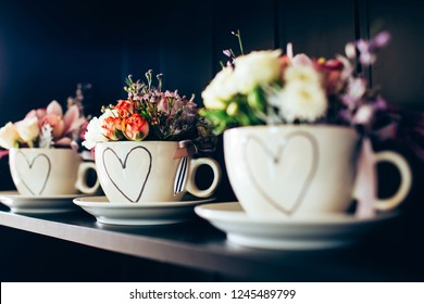 white cup with flowers on the black shelf. cup with roses for Mother's Day. Valentine's Day.