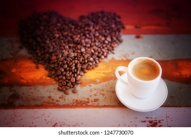 white cup of fresh coffee and coffee beans in a heart shape