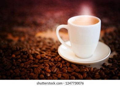 white cup of fresh coffee on table with coffee beans