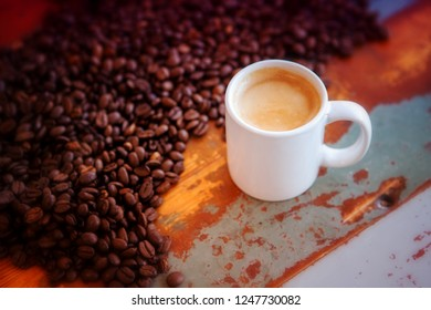 white cup of fresh coffee on wooden table with coffee beans