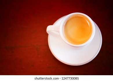 white cup of fresh coffee on old vintage wooden table