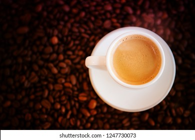 white cup with freshly brewed coffee and whole coffee beans