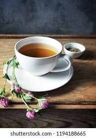 A white cup of herbal tea from clover flowers on wooden table.