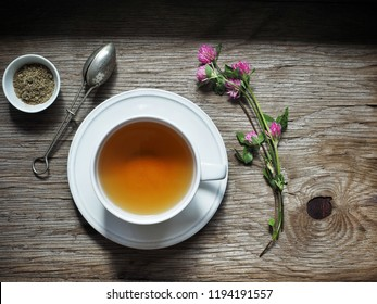A white cup of herbal tea from clover flowers on wooden table. Overhead shot.