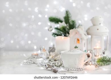 White cup of hot cappuccino coffee on holiday white and silver background, Christmas concept