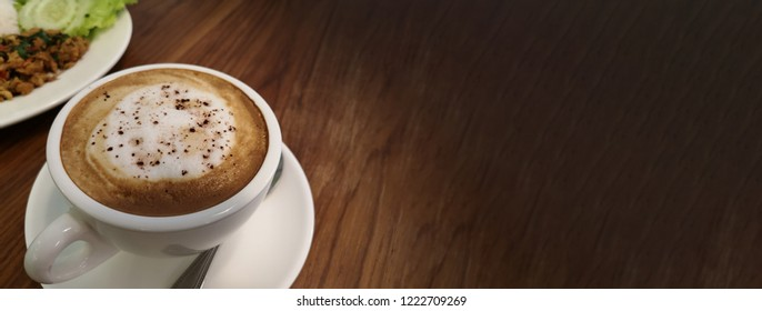 The white cup of hot capuchino with the white foam and spring cinnamon on the top of coffee. Side view on the wooden table with the copy space. Selective focus and the blur background of thai food.