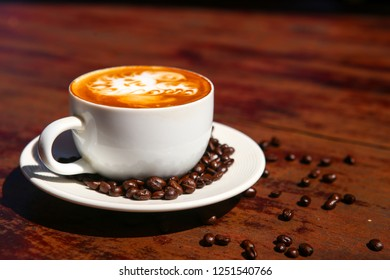The white cup of hot capuchino with the white foam and spring cinnamon on the top of coffee. Side view on the wooden table with the copy space