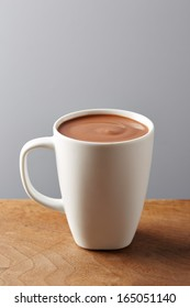 White cup of hot chocolate on wooden table