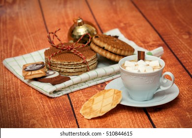A white cup of hot cocoa with marshmallows and cookies