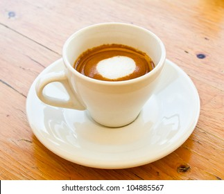 White cup of hot coffee cappuccino on brown wooden table