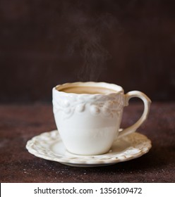 White cup of hot coffee with cream on brown background