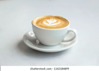 White cup with hot coffee and milk, glass cup and saucer