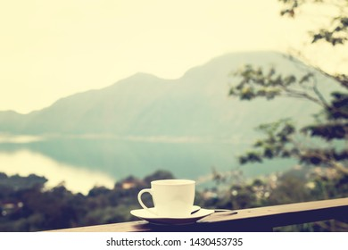 White cup of hot coffee on nature background. Bali island. Volcano Batur. Asia.