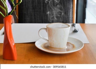 white cup of hot coffee on wooden in coffee shop