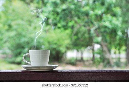 white cup of hot coffee on natural green background,