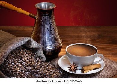 White cup of hot coffee with roasted beans and turkish coffee pot on wooden table.
