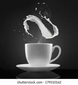 white cup with hot liquid and milk splash on black