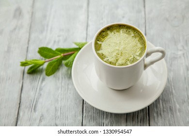 white cup of hot matcha green tea latte and branch of mint on light wooden background
