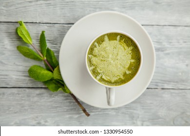white cup of hot matcha green tea latte and branch of mint on light wooden background, top view