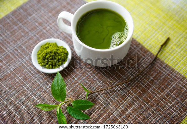 White Cup with hot tea and dry powder of Japanese green tea matcha on a white saucer on a brown background combined with green, with a checkered texture. The set is decorated with a branch with green