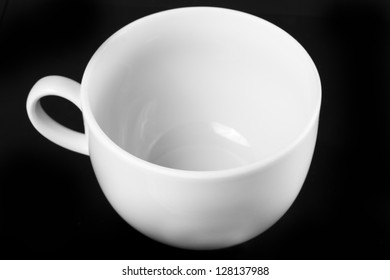 White cup isolated on black background. Black and white photo.