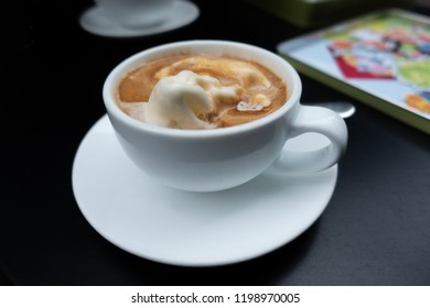White Cup of  Italian coffee-based dessert Affogato coffee in table. Form of a scoop of vanilla gelato or ice cream topped or drowned with a shot of hot espresso. Black table surface.