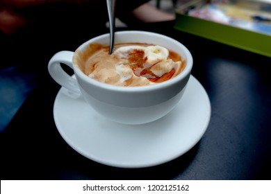 White Cup of Italian coffee-based dessert Affogato coffee with dessert spoon in table. Form of a scoop of gelato or ice cream topped or drowned with a shot of hot espresso. Black table surface.