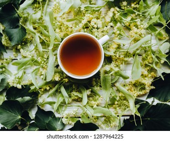 White cup of linden tea on linden blossom background. Herbal medicine. Top view.