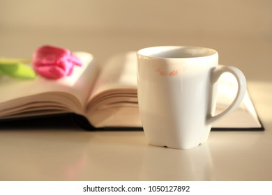 White cup or mug with red lipstick mark, interesting book and tulip flower, morning reading