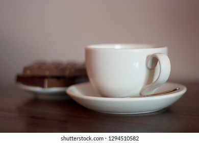 White cup on a saucer with metal spoon with chocolate biscuits in the background.  Coffee shop, tea shop, cuppa with friends, relaxing, take a break concepts.