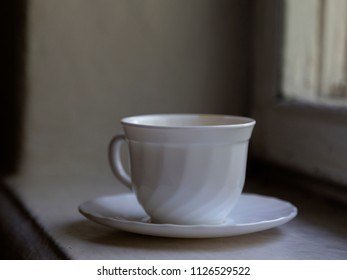 White cup on a windowsill. The image is made in a soft scattering light with a slight blur.
