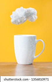 White cup on a wooden table. White cloud of cotton wool over a cup on a yellow background. Steam raising concept