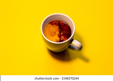 White cup on yellow background, black tea and milk.