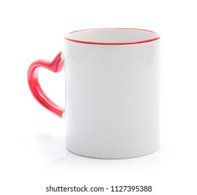 White cup with red rim and handle in heart shape isolated on a white background