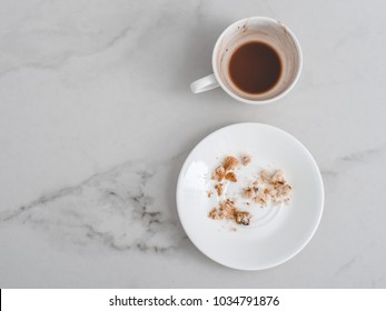 White cup with the remains of cocoa beverage and a white saucer with cookie crumbs on a white marble table