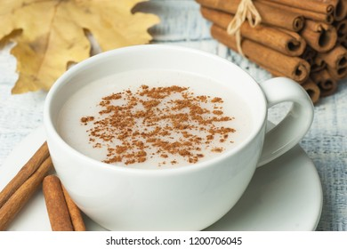 white cup of salep milky hot drink of Turkey with cinnamon powder and sticks healthy spice and autumn winter leaf on white rustic vintage wooden table. Sahlep background