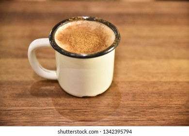 white cup of salep milky hot drink of Turkey with cinnamon and cookie